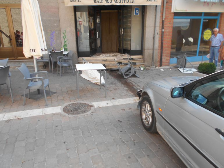 Vehículo accidentado y estado en el que ha quedado la terraza y el acceso del establecimiento con el que se ha empotrado