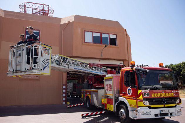 Luis Palma (i) y Daniel Arreza (d), los bomberos que ayer rescataron a una niña de 5 años que se encontraba colgada del balcón de un octavo piso de Málaga, manipulan la autoescala de treinta metros con la que accedieron a la fachada del edificio