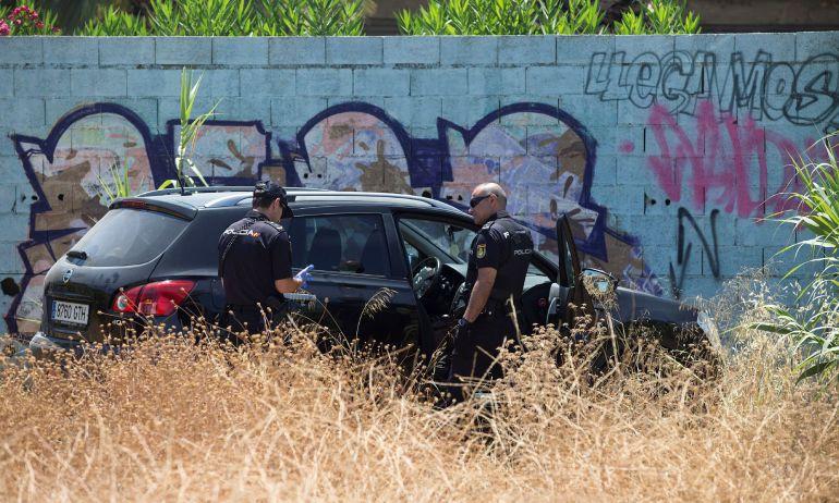 Agentes de la Policía Nacional registran el coche en el que ha sido hallado muerto un hombre de 43 años tras agredir a su pareja, de 42 años, que ha sido trasladada a un hospital, en las inmediaciones del aparcamiento de la zona de la Avenida de Europa en Málaga