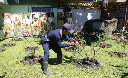 Un hombre limpia el 'Jardin de la Rosas' en el que se encontraron los cuerpos de los seis sacerdotes jesuitas.