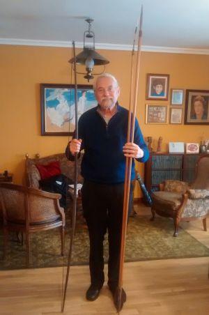 Enrique Martínez Reguera en su casa de Madrid con un arco y dos lanzas traídas de uno de sus viajes a Brasil.