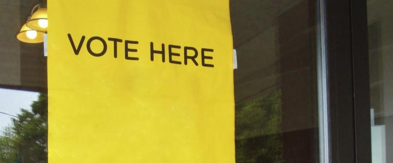 Indicaciones, en inglés, de la entrada de un lugar donde se recoge el voto.