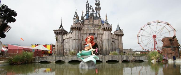 El palacio de Dismaland parodia al de Disney, al igual que lo hace la sirenita distorsionada sobre un estanque enfanganado.