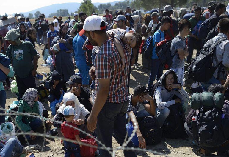 VAS21 GEVGELIJA (MACEDONIA) 28/08/2015.- Inmigrantes esperan en el paso fronterizo de Macedonia y Grecia cerca de Gevgelija hoy, 28 de agosto de 2015. Mientras los países de la Unión Europea discuten, Europa está a un paso de contabilizar las 300.000 llegadas de inmigrantes y refugiados desde que empezó este año y 3.000 personas diarias estarán en ruta hacia Serbia en los próximos días, según la Agencia de las Naciones Unidas para los Refugiados (ACNUR). EFE/Vassil Donev