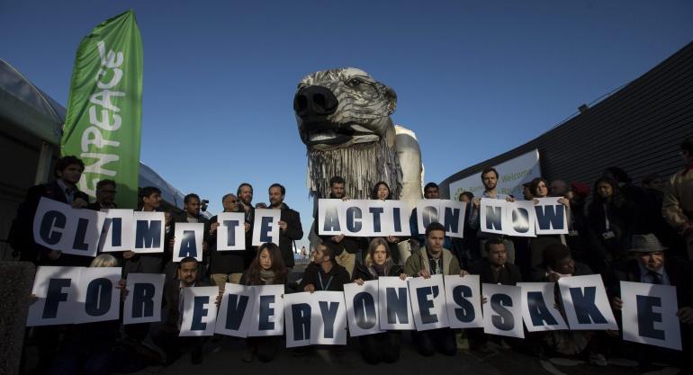 """Un grupo de representantes de Greenpeace muestran una pancarta en la que se lee """"Acción por el clima ahora para el bien de todos"""" delante de una réplica de un oso polar gigante, durante un acto de Greenpeace para aumentar la conciencia sobre el cambio climático en la Conferencia del clima COP21"""