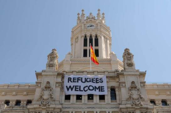 Cartel que reza 'Bienvenidos Refugiados' en la fachada principal del ayuntamiento de Madrid