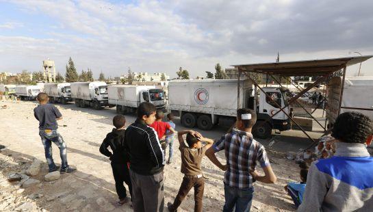 Varios camiones de la Media Luna Roja con ayuda humanitaria entran en el campo de refugiados del campo de refugiados de la ciudad de Douma, en el distrito de Damasco Siria