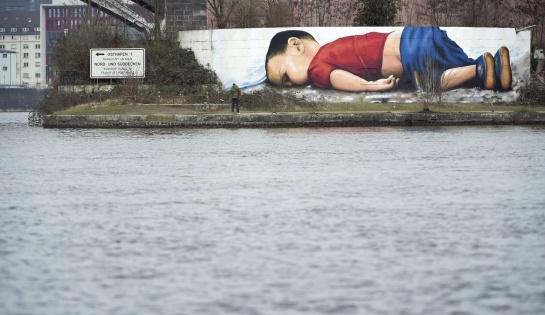 Vista general de un grafiti de Aylan Kurdi, el niño sirio que murió ahogado en las playas de Turquía y cuya fotografía se ha convertido en símbolo de la crisis de refugiados, en el puerto de Fráncfort (Alemania)
