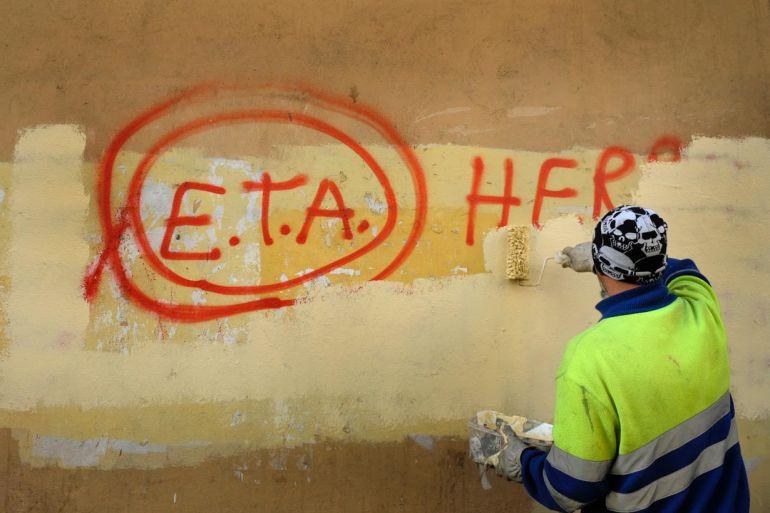 Un operario pinta sobre una pintada de ETA en las calles de Bilbao