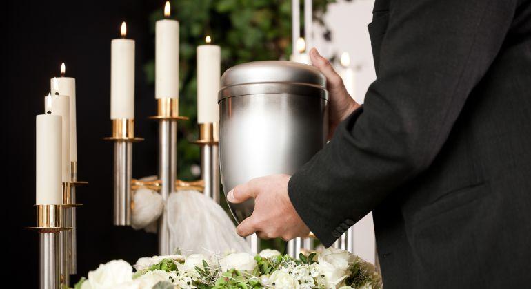 Imagen de un hombre sosteniendo una urna funeraria rodeado de velas y flores.