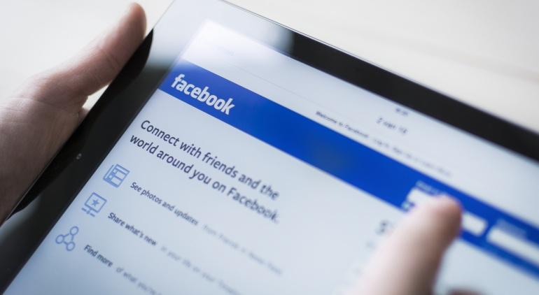 Imagen de una persona sosteniendo una tableta con la web de Facebook en la pantalla.