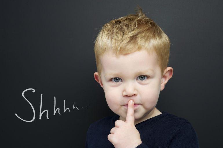 Niño con el dedo en la boca, símbolo de pedir silencio.