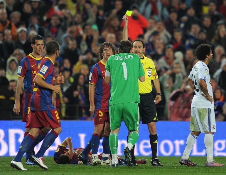 Iturralde enseña la tarjeta amarilla a Casillas durante un Clásico