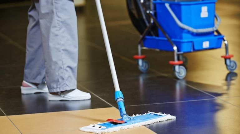 Imagen de una trabajadora de la limpieza pasando la mopa en el suelo de un edificio.