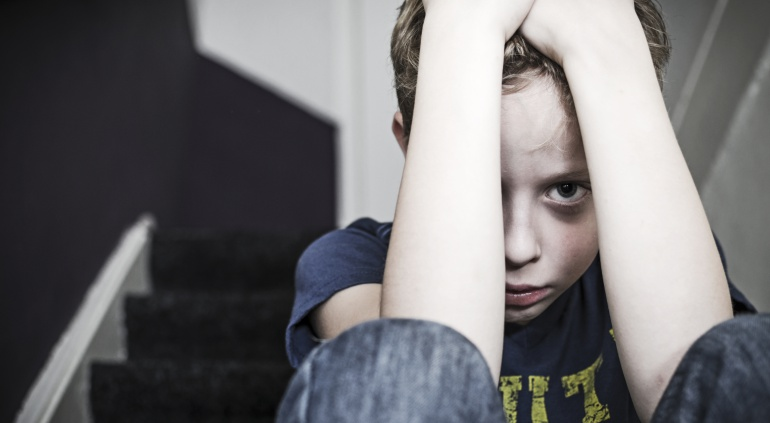 Imagen de un niño, con rostro atemorizado, que se tapa la cara con los brazos.