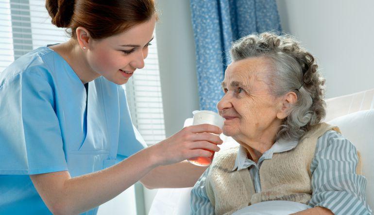 Una cuidadora da de beber a una señora mayor.