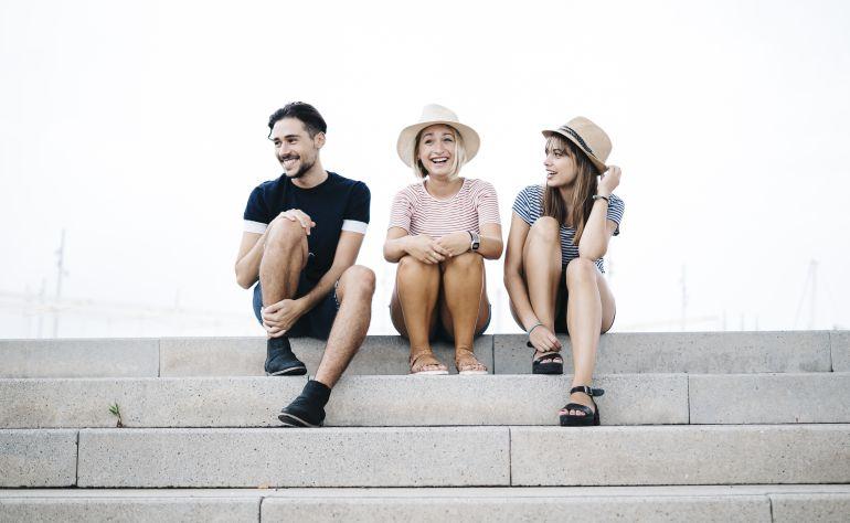 Tres jóvenes sonríen sentados en una escalera.