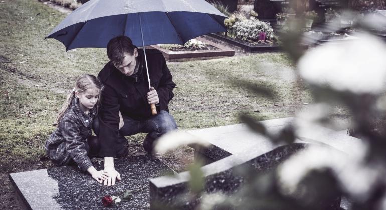 Un padre y su hija depositan una flor en una tumba de un cementerio.