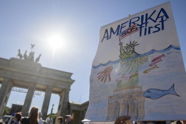 Un manifestante sostiene un cartel en el que se lee 'America SOS primero', durante las protestas contra la salida de Estados Unidos del Acuerdo de París
