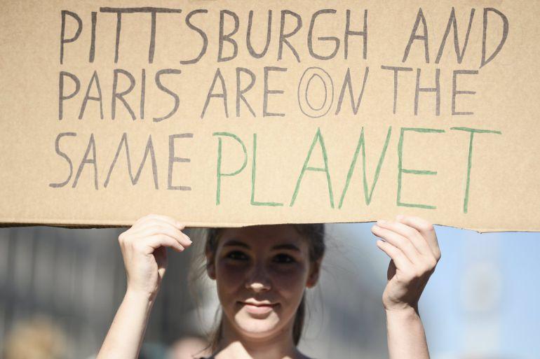 Una manifestante sostiene una pancarta en la que se lee 'Pittburgh y París están en el mismo planeta', durante las protestas contra la salida de Estados Unidos del Acuerdo de París
