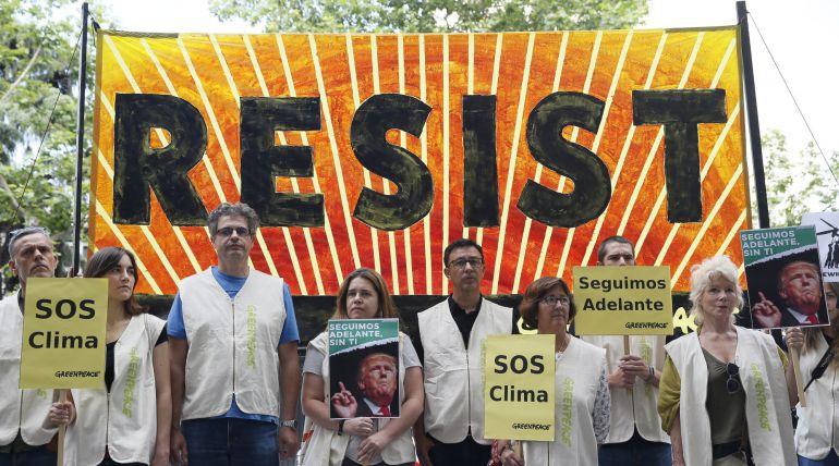 Participantes en la concentración convocada por Greenpeace frente a la Embajada de Estados Unidos para protestar por la decisión del presidente de Estados Unidos, Donald Trump, de sacar a su país del Acuerdo de París.