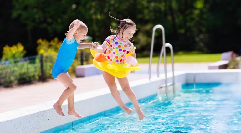 Dos niños saltan a una piscina.