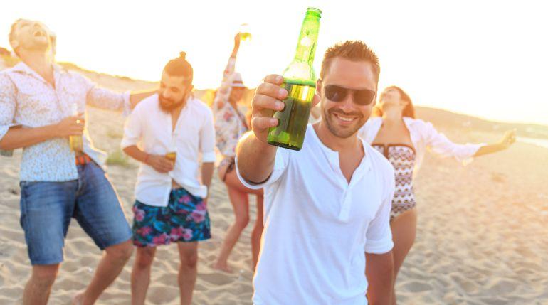 Imagen de un grupo de jóvenes bebiendo alcohol en la playa.