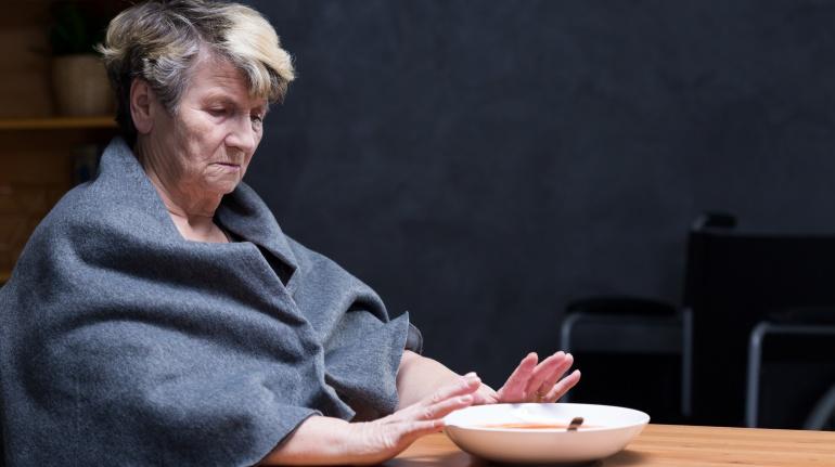 Imagen de una señora mayor comiendo sola y calentándose las manos con el plato de sopa.
