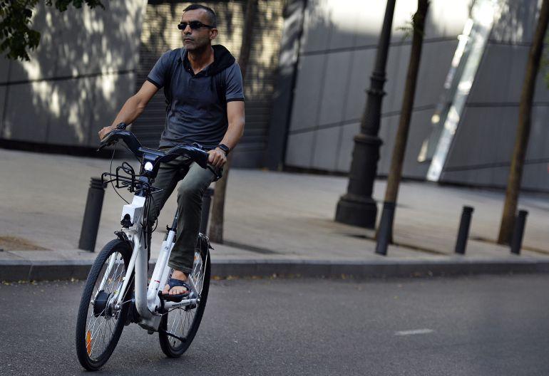 Usuario de bicicleta urbana circulando por una calle en ciudad.