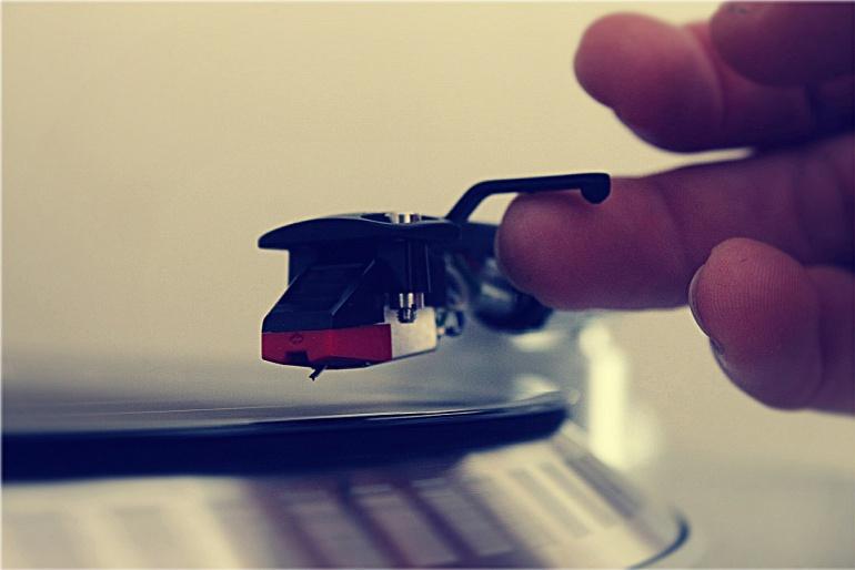 Una persona a punto de poner pinchar un disco en un tocadiscos