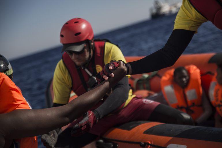 Un miembro de Proactiva Open Arms ayuda a un migrante a subirse a la embarcación de rescate.