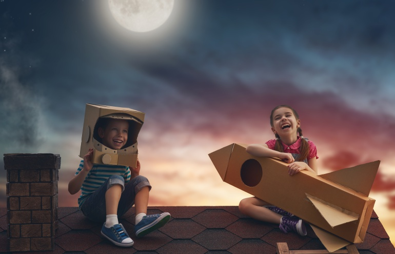 Imagen de dos niños en un tejado jugando a ser astronautas.