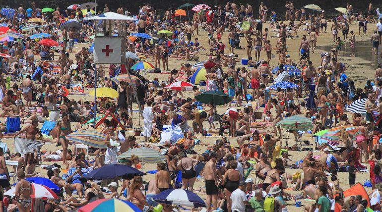 Vistas a una playa repleta de turistas.