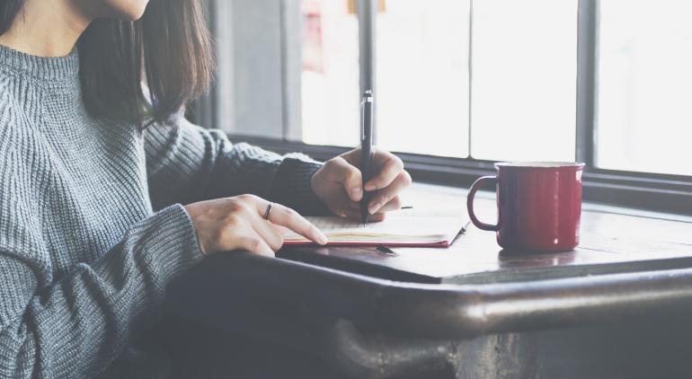 Una mujer escribiendo en un cuaderno