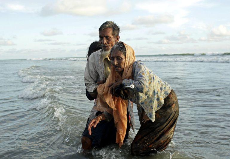 Tres refugiados de la etnia rohinyá, caminan hacia la orilla tras cruzar el río Naf, que marca la frontera de Bangladesh y Birmania