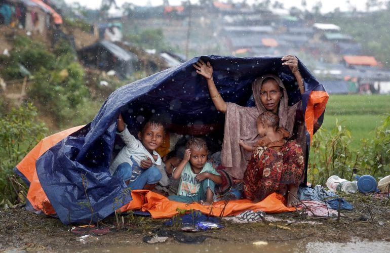 Refugiados Rohingya se refugian de la lluvia en un campo de Bangladesh.