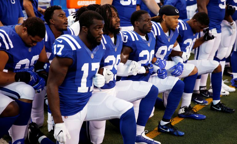 Los jugadores de los Indianapolis Colts se ponen de rodillas durante la ceremonia del himno