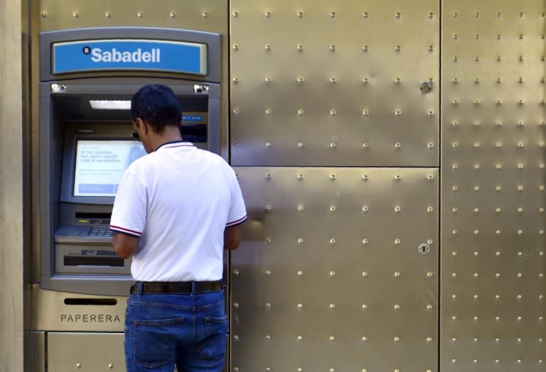 Un hombre frente a un cajero del Banco Sabadell