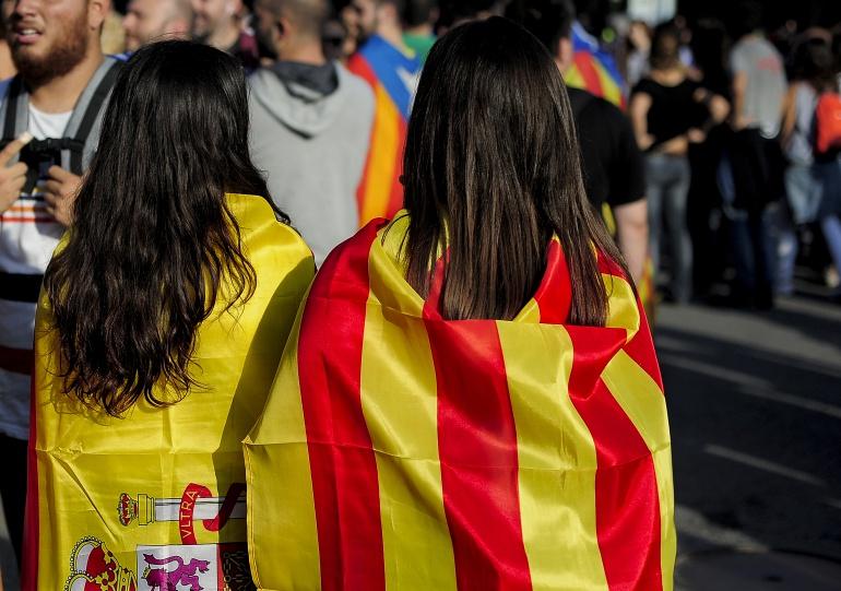 Dos chicas con banderas de España y Cataluña a la espalda