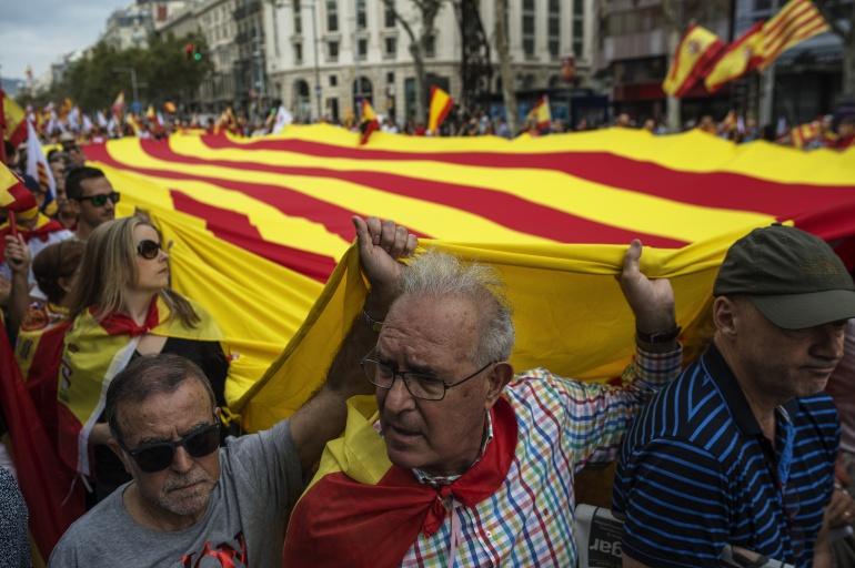 Manifestantes portan una gran bandera catalana en Barcelona