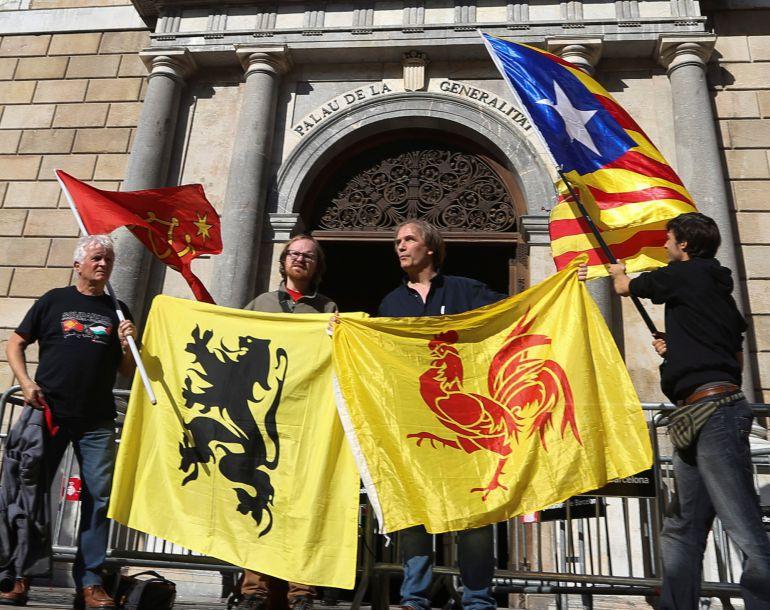 Cuatro personas sostienen las banderas (de izda a dcha) de las regiones de Occitania, Flandes, Valonia y la estelada, ante el Palau de la Generalitat, en el primer día laborable tras la puesta en marcha del artículo 155 de la Constitución para hacer frente al desafío secesionista en Cataluña.