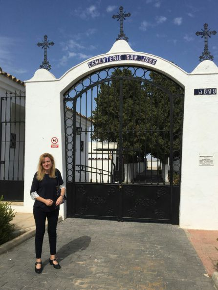 Mari Carmen frente a las rejas negras que dan entrada al cementerio de La Puebla de Cazalla (Sevilla).