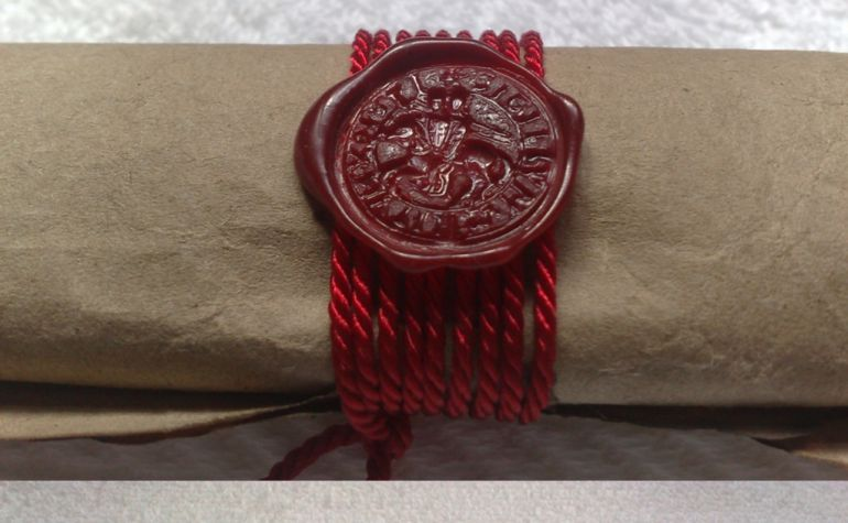 Manuscrito en pergamino sellado con nueve vueltas de hilo de seda y lacre rojo. Se puede distinguir el sello de la Orden.