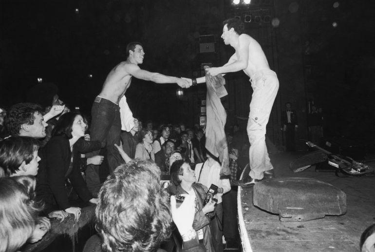 Joe Strummer (1952 - 2002), líder de The Clash, intercambia la camiseta con un seguidor en The Rainbow Theatre de Londres durante un concierto el 14 de mayo de 1977