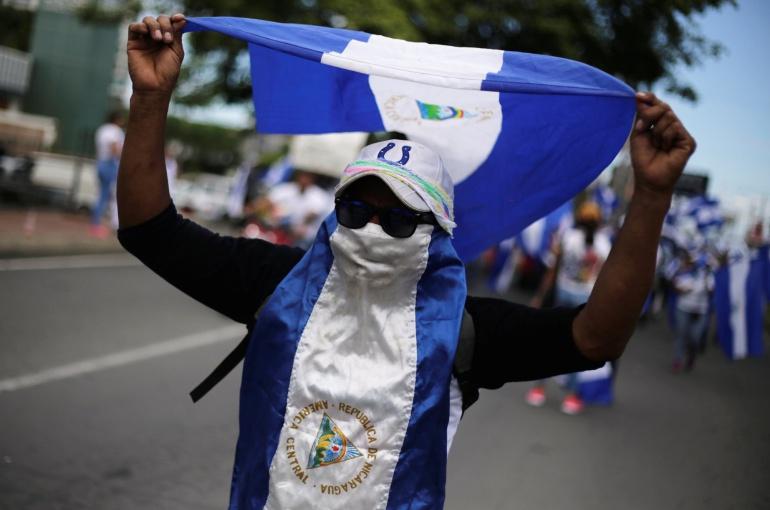 Un hombre camuflado con la bandera de Nicaragua y gafas de sol durante una de las manifestaciones en contra del Gobierno de Daniel Ortega
