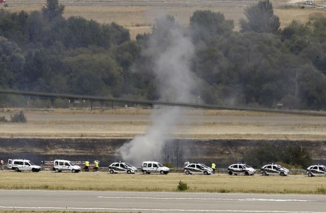 Varios coches de Policía apostados cerca del lugar de la tragedia, donde se vislumbran enormes columnas de humo