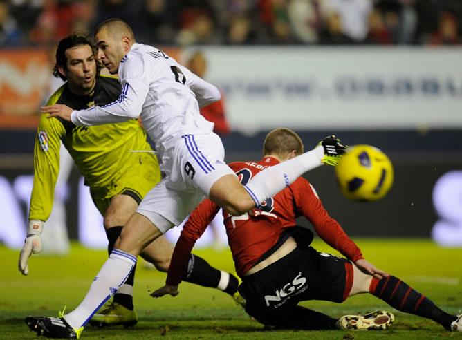 Benzema lucha por el balón ante el portero del Osasuna durante el partido de la 21ª jornada de la Liga BBVA