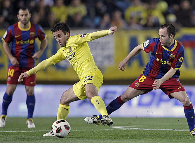 El delantero italiano del Villarreal Giuseppe Rossi lucha el balón con Iniesta