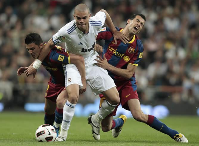 Pepe defiende un balón ante Busquets y Villa
