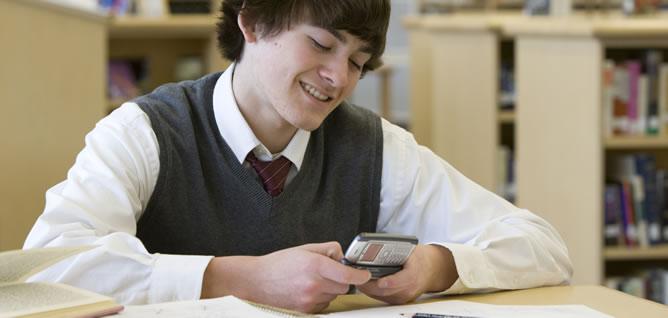Un joven estudiante con su móvil en la biblioteca